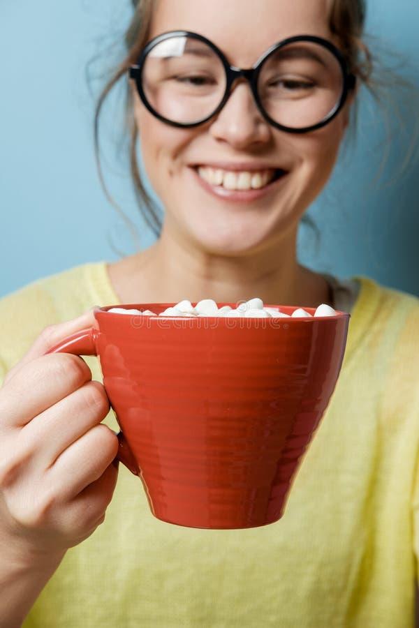 Mujer joven del empollón divertido con una taza roja con cacao y la melcocha imagenes de archivo
