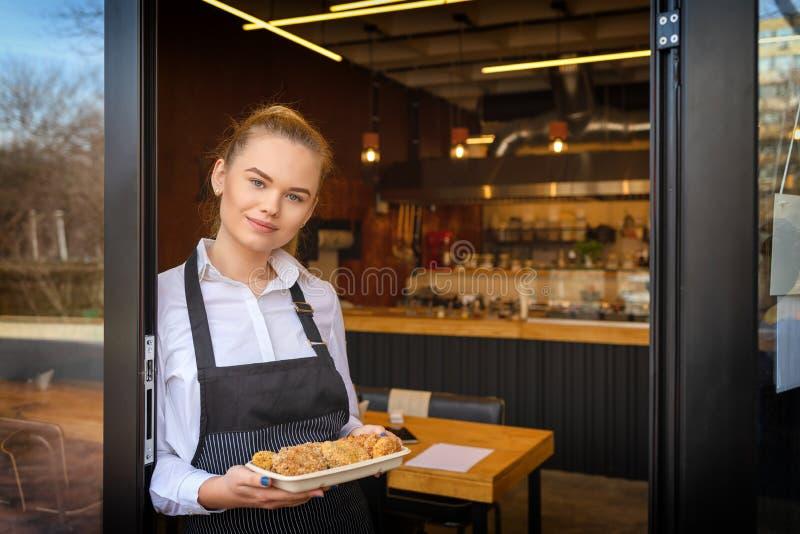 Mujer joven del empresario en el pequeño restaurante del negocio familiar que se inclina en la gente de invitación de la puerta d foto de archivo
