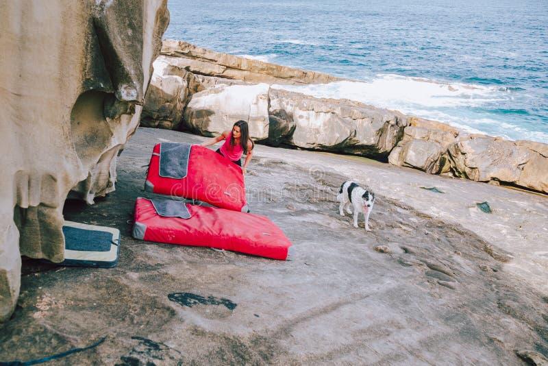 Mujer joven del escalador que coloca el equipo de seguridad para bouldering fotos de archivo libres de regalías