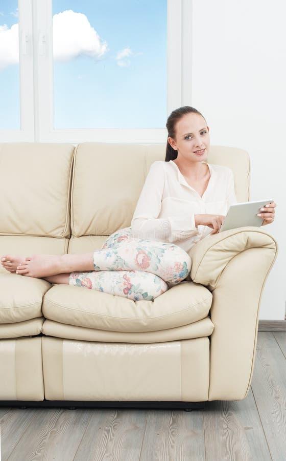 Mujer joven del estudiante con la tableta en el sofá imagen de archivo