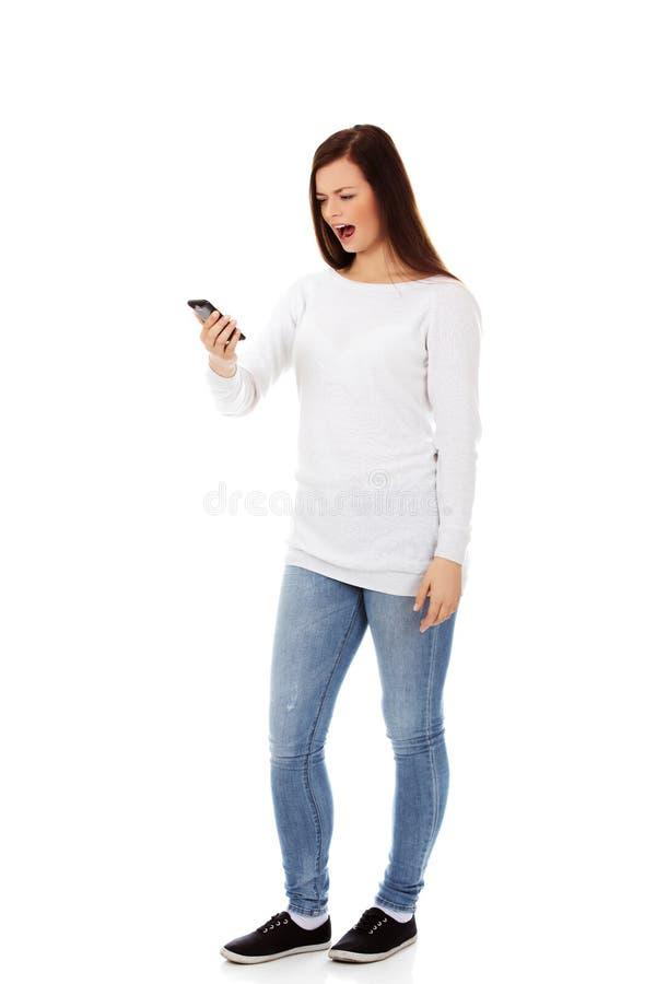Mujer joven del estudiante que grita al teléfono móvil fotografía de archivo