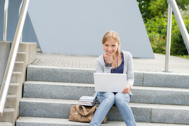 Mujer joven del estudiante que se sienta en pasos de progresión de la universidad foto de archivo libre de regalías