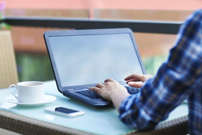 Mujer joven del freelancer que usa el ordenador portátil que se sienta en la etiqueta del café foto de archivo