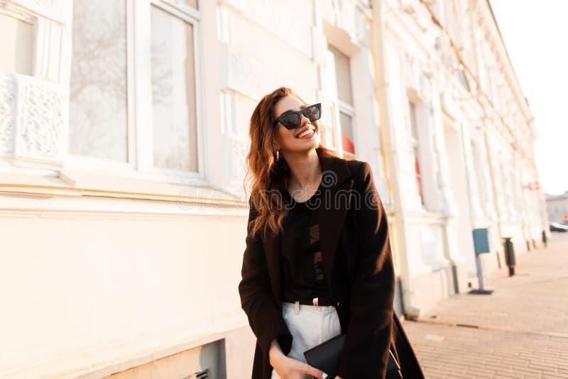 Mujer joven del inconformista alegre divertido en gafas de sol elegantes con la capa de moda en los vaqueros blancos con un bolso fotos de archivo libres de regalías