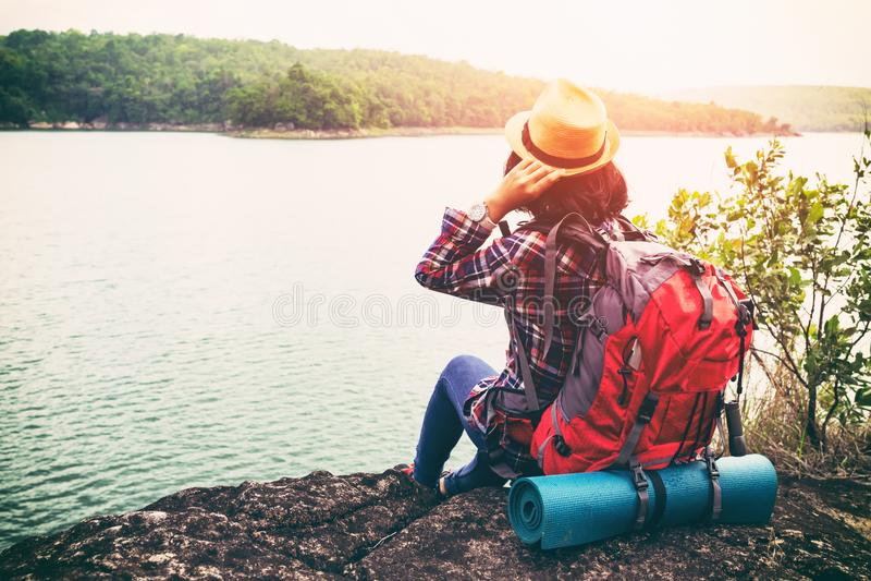 Mujer joven del inconformista con el backpacker que se sienta en el goce de piedra fotos de archivo