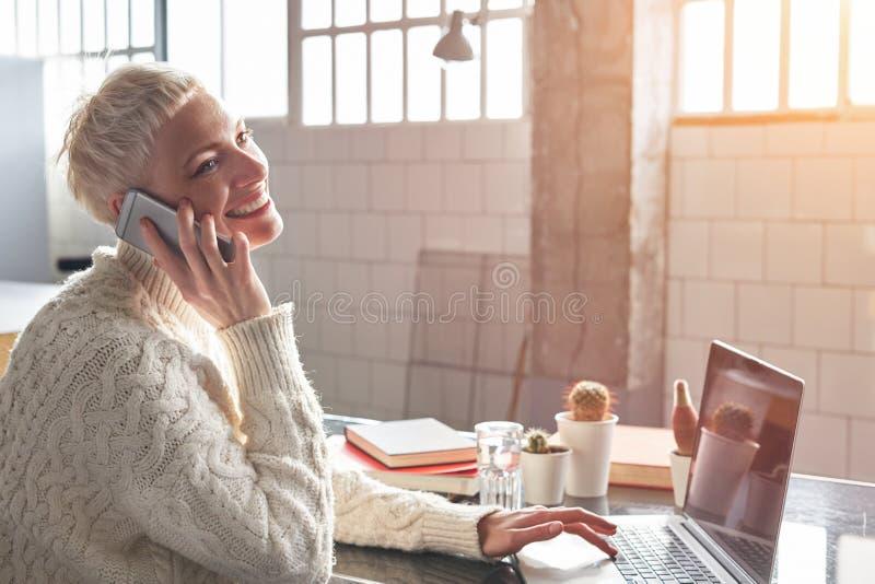 Mujer joven del inconformista con el pelo corto rubio que sonríe y que habla por smartphone móvil, trabajando en el ordenador por foto de archivo
