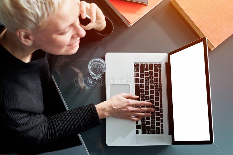 Mujer joven del inconformista con el pelo corto rubio que sonríe y que habla por smartphone móvil, trabajando en el ordenador por fotografía de archivo