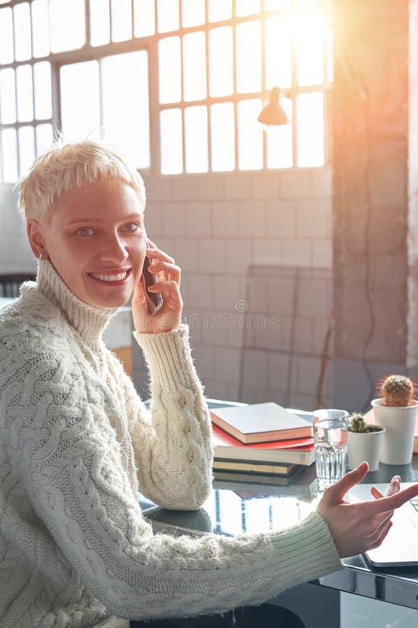 Mujer joven del inconformista con el pelo corto rubio que sonríe y que trabaja en el ordenador portátil, sentándose en la oficina imagen de archivo