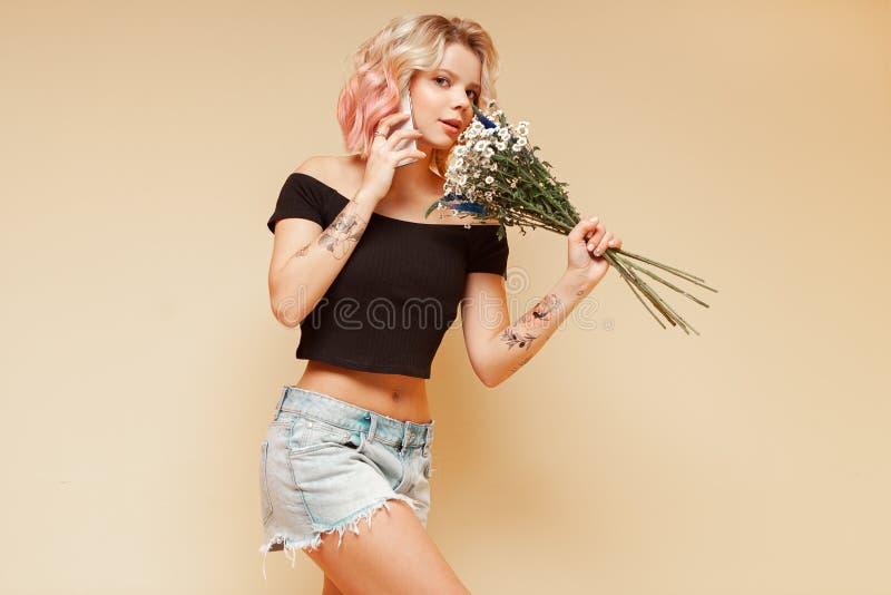 Mujer joven del inconformista con los pelos rizados coloreados y tatuar la sonrisa y hablar en el teléfono, sosteniendo las flore foto de archivo libre de regalías