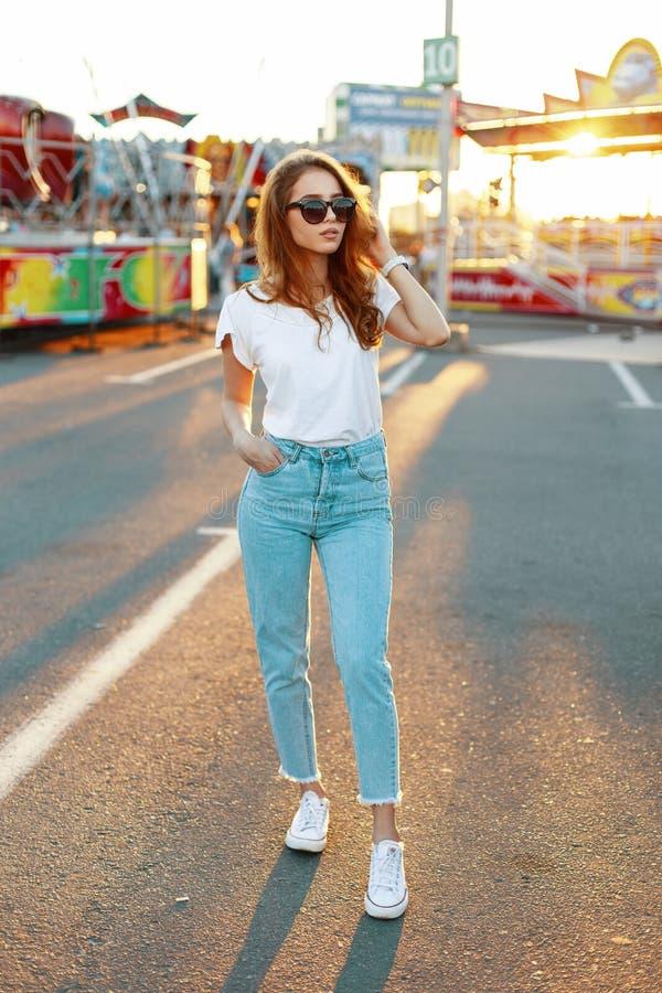 Mujer joven del inconformista en camiseta elegante en gafas de sol de moda en tejanos en las zapatillas de deporte que presentan  fotos de archivo libres de regalías