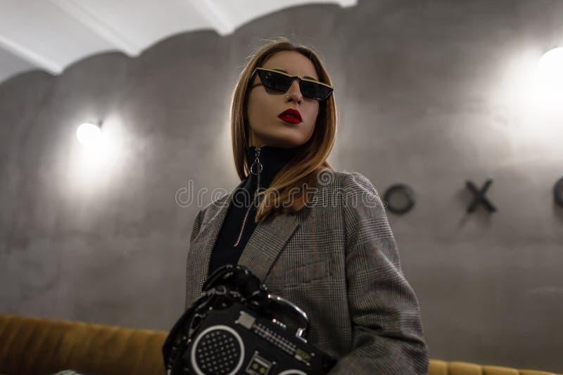 Mujer joven del inconformista moderno en gafas de sol elegantes con un nariz-oído de los rojo-labios en una chaqueta elegante gri imagen de archivo libre de regalías
