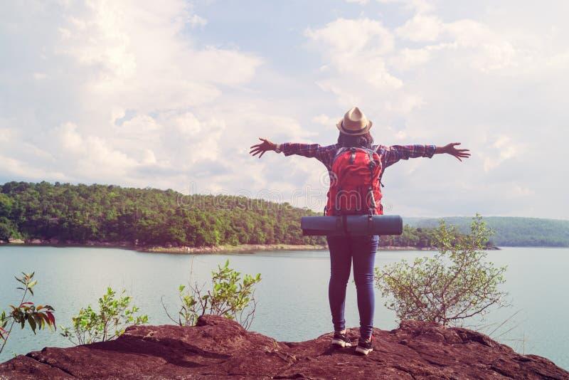 Mujer joven del inconformista que se coloca en piedra en las manos de la demostración de la orilla del lago imagen de archivo libre de regalías