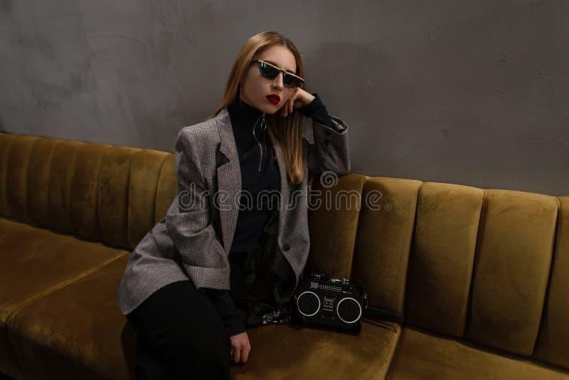 Mujer joven del inconformista que sorprende con los labios rojos con una nariz perforada en una chaqueta a cuadros en estilo retr imágenes de archivo libres de regalías