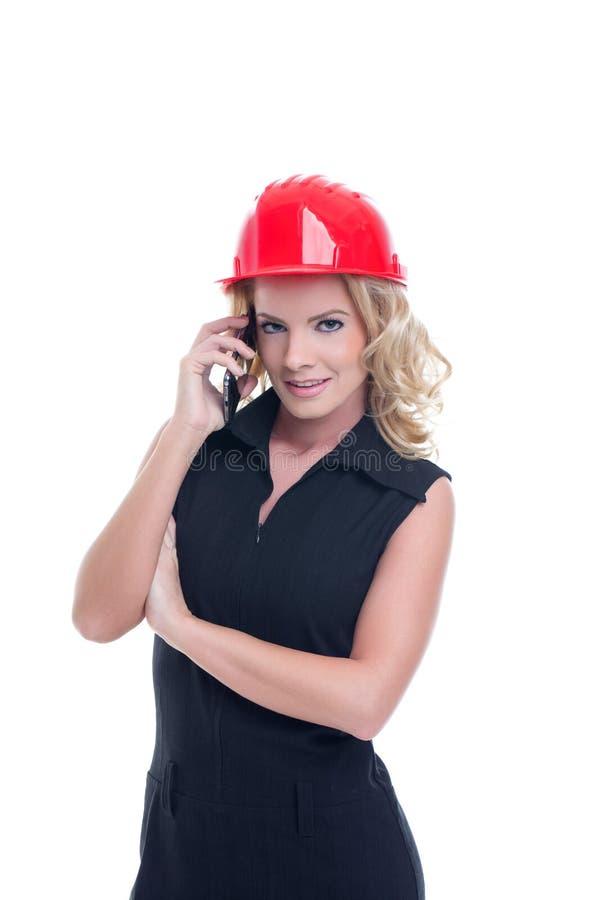 Mujer joven del ingeniero en casco rojo que llama aislado fotografía de archivo