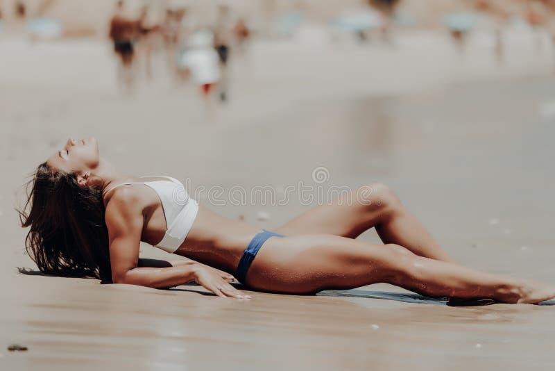 Mujer joven del latín de la belleza que miente en la arena la costa del océano foto de archivo libre de regalías
