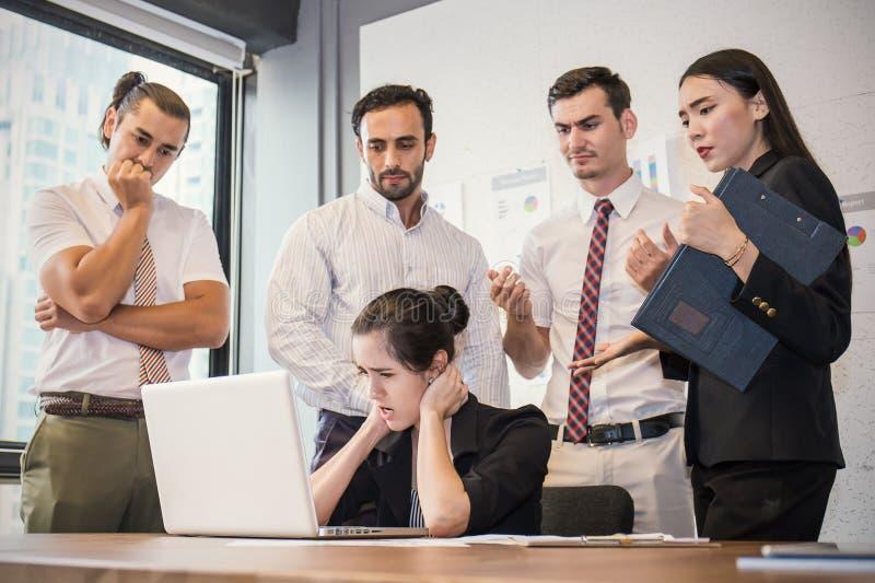 Mujer joven del negocio agotador con sus manos en su cabeza delante de su ordenador portátil imagenes de archivo