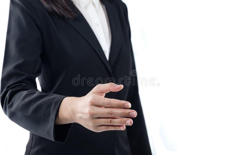 Mujer joven del negocio con la mano abierta lista para sellar un trato, apretón de manos con los hombres de negocios, etiqueta de foto de archivo libre de regalías