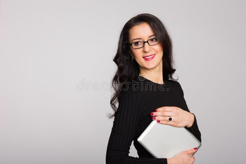 Mujer joven del negocio feliz que sostiene una tableta foto de archivo libre de regalías