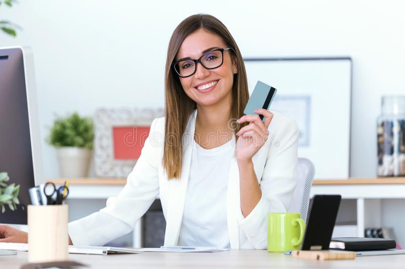 Mujer joven del negocio que usa la tarjeta de crédito en tienda en línea foto de archivo