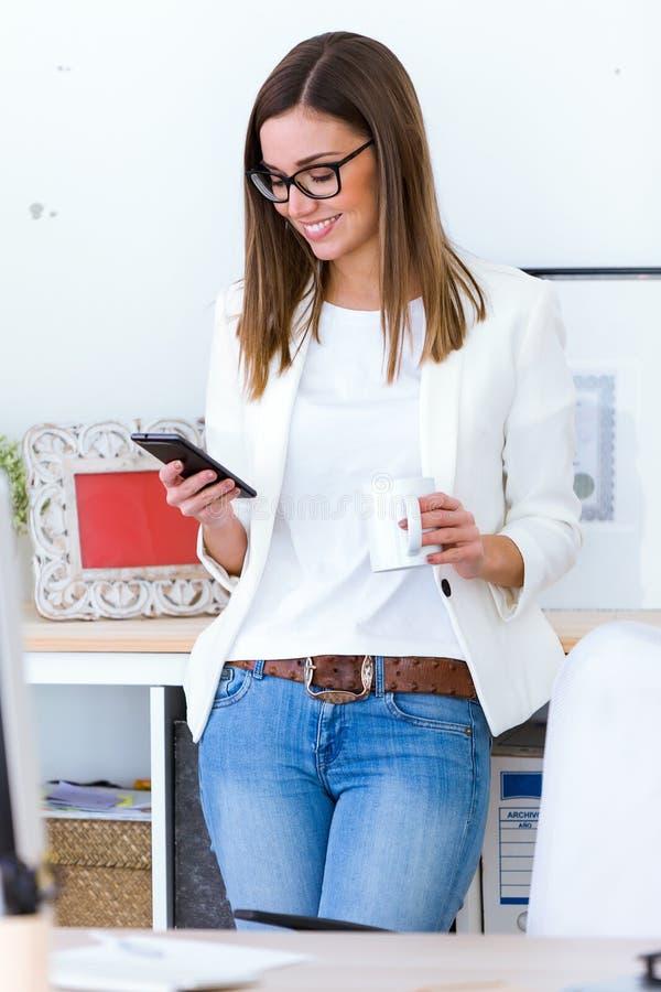 Mujer joven del negocio que usa su teléfono móvil en la oficina imágenes de archivo libres de regalías