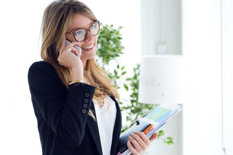 Mujer joven del negocio que usa su teléfono móvil en la oficina imagen de archivo libre de regalías