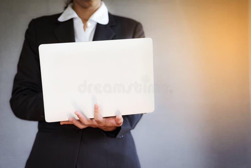 Mujer joven del negocio usando el ordenador portátil en la oficina imagen de archivo