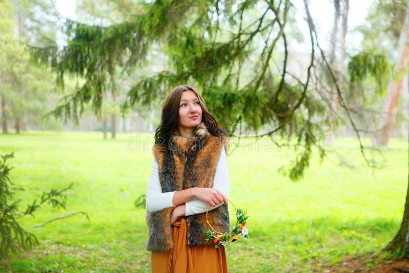 Mujer joven del otoño con la guirnalda de la flor en sus manos y en abrigo de pieles al aire libre imagen de archivo