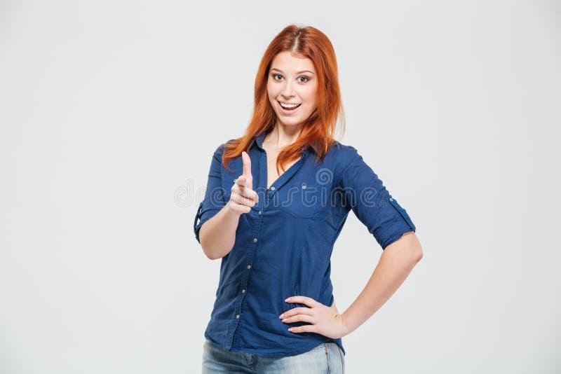 Mujer joven del pelirrojo atractivo alegre que señala en usted imagen de archivo libre de regalías