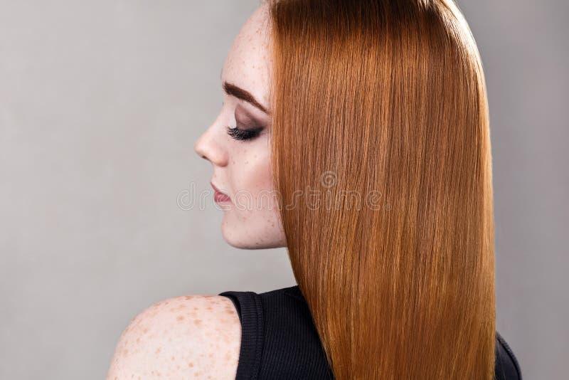 Mujer joven del pelirrojo con el pelo brillante largo foto de archivo