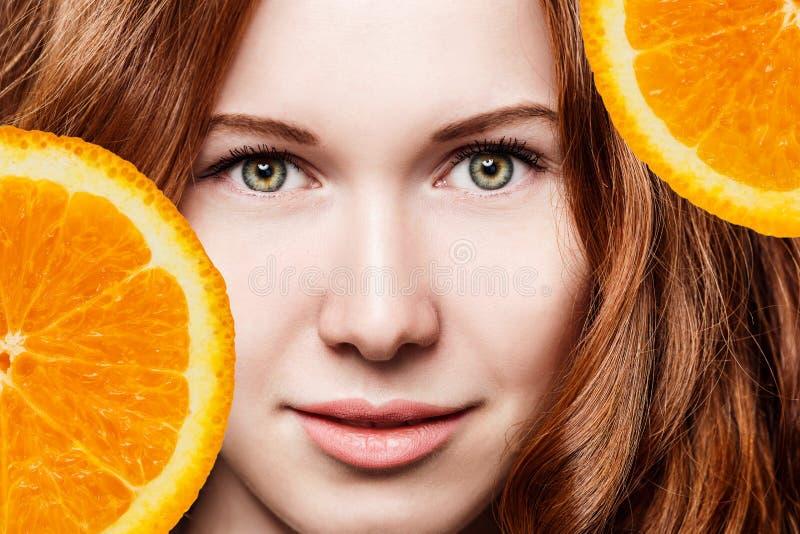 Mujer joven del pelirrojo con las rebanadas anaranjadas de la fruta fotografía de archivo libre de regalías