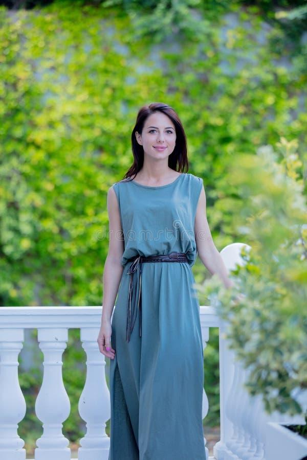 Mujer joven del pelirrojo en el vestido que se coloca en jardín, foto de archivo libre de regalías