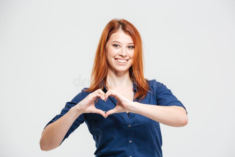 Mujer joven del pelirrojo hermoso alegre que hace el corazón por las manos foto de archivo libre de regalías