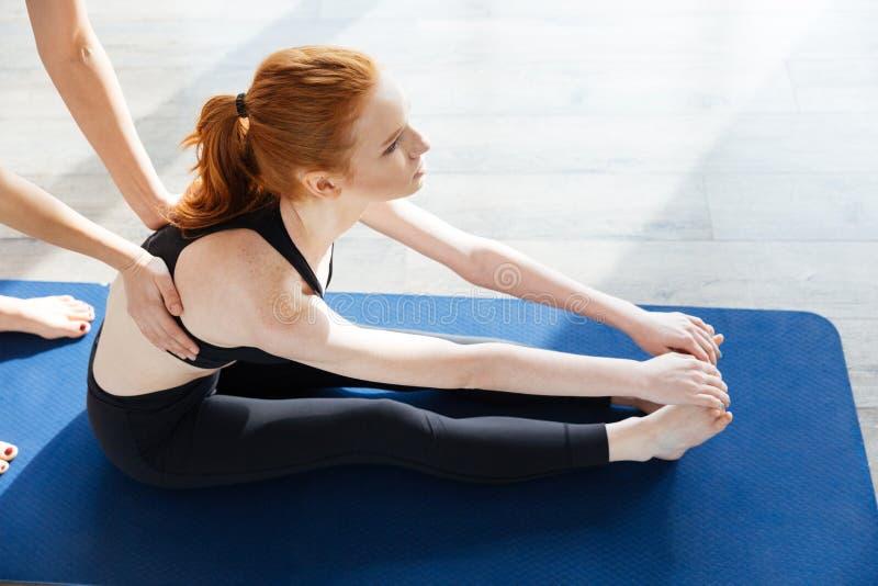 Mujer joven del pelirrojo precioso que hace yoga con el instructor personal fotos de archivo libres de regalías