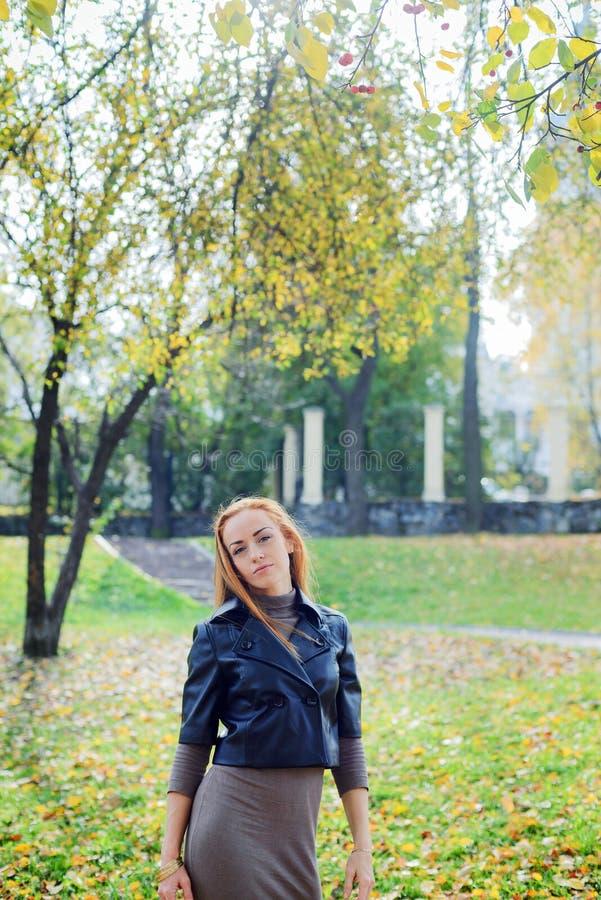Mujer joven del pelirrojo que camina en parque del otoño imágenes de archivo libres de regalías