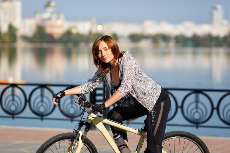 Mujer joven del pelirrojo que monta una bici en el terraplén Gente activa al aire libre Forma de vida del deporte fotografía de archivo