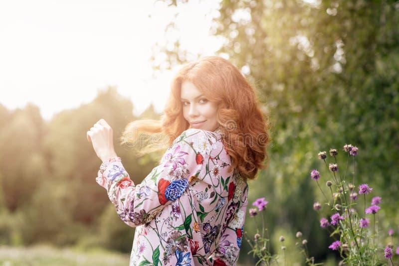 Mujer joven del pelirrojo que presenta en parque del verano fotografía de archivo
