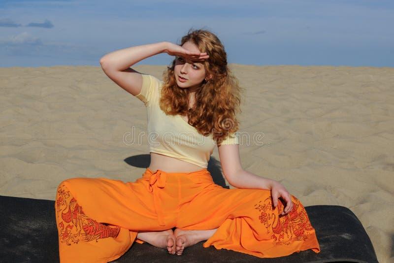 Mujer joven del pelirrojo que se sienta en actitud de la yoga del titli del purna en el beac imágenes de archivo libres de regalías