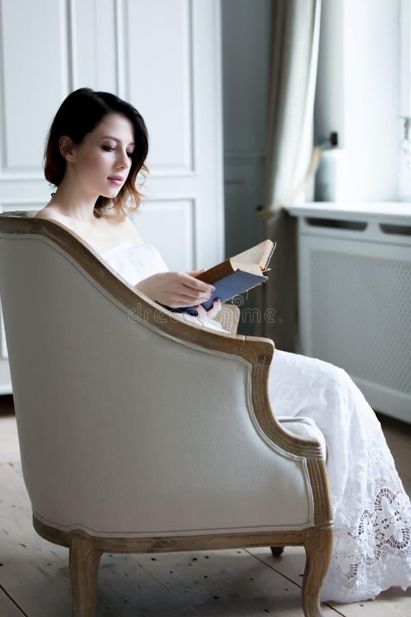 Mujer joven del pelirrojo que se sienta en libro de lectura de la silla imagenes de archivo