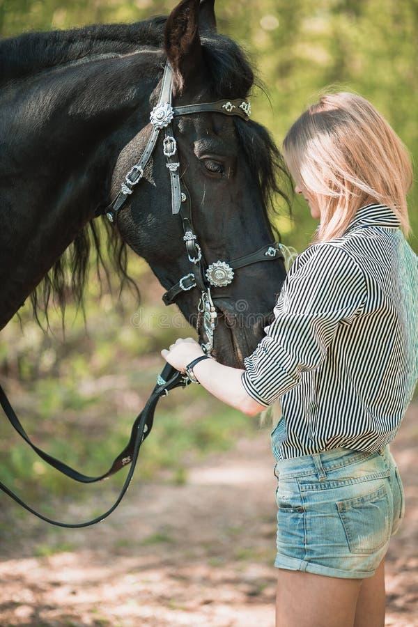 Mujer joven del pelo largo con un caballo al aire libre fotografía de archivo libre de regalías