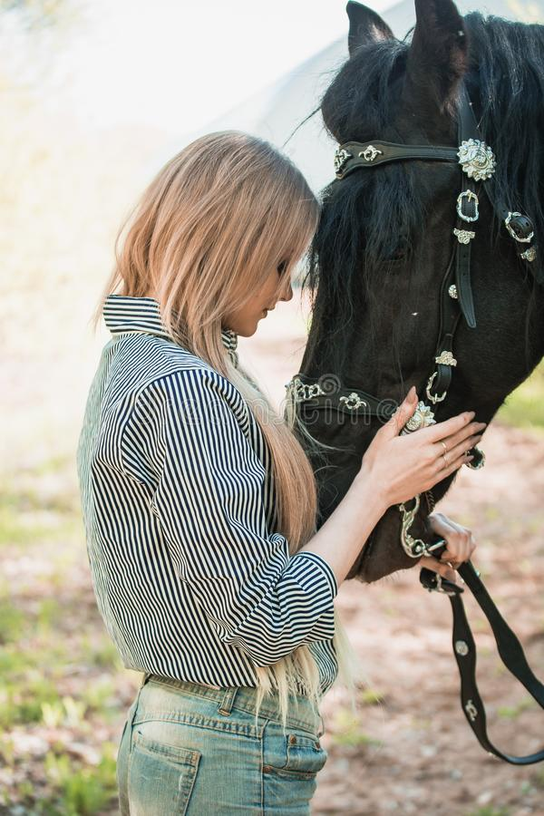 Mujer joven del pelo largo con un caballo al aire libre foto de archivo