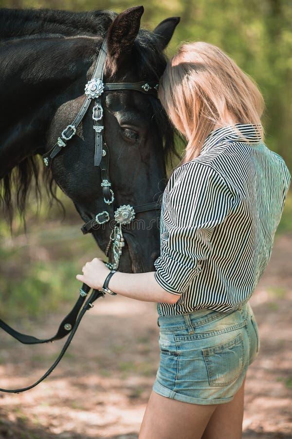 Mujer joven del pelo largo con un caballo al aire libre imágenes de archivo libres de regalías