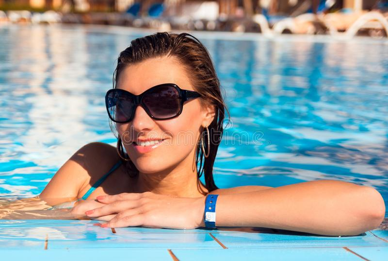 Mujer joven del pelo largo hermoso en el agua azul en gafas de sol, cierre encima del retrato al aire libre imagen de archivo libre de regalías