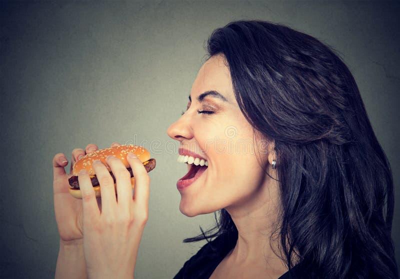 Mujer joven del perfil lateral que come una hamburguesa sabrosa fotos de archivo libres de regalías