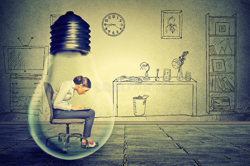 Mujer joven del perfil lateral que usa el trabajo en el ordenador que se sienta dentro de la lámpara eléctrica foto de archivo libre de regalías