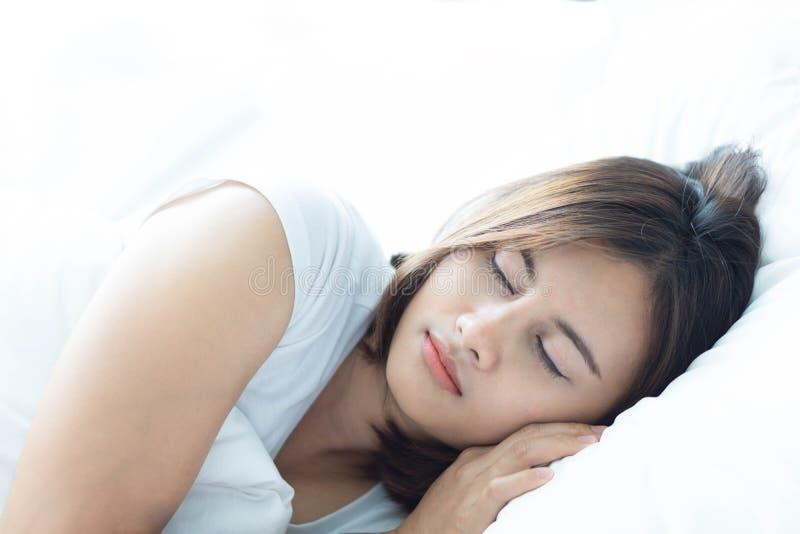 Mujer joven del primer que duerme con la cara feliz en la cama, foco selectivo fotos de archivo
