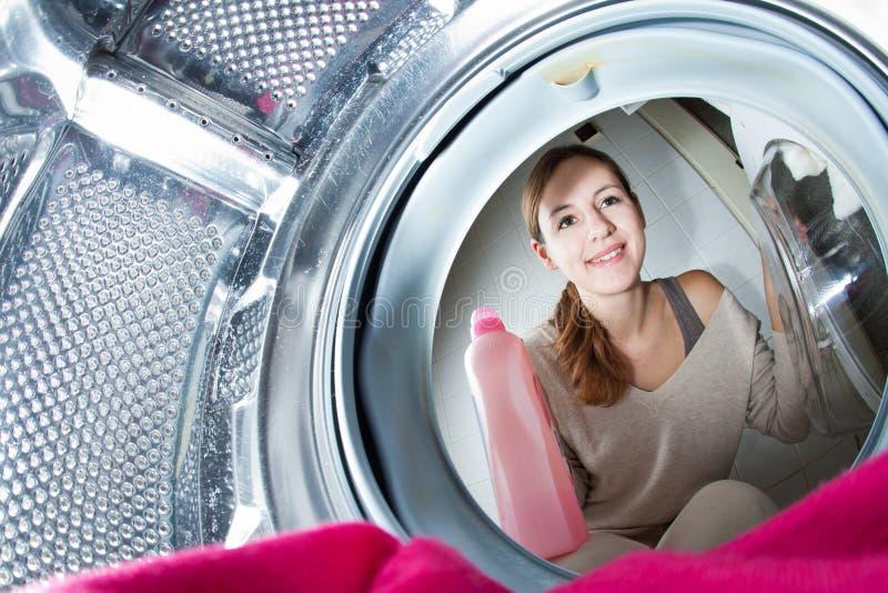 Mujer joven del quehacer doméstico que hace el lavadero foto de archivo libre de regalías