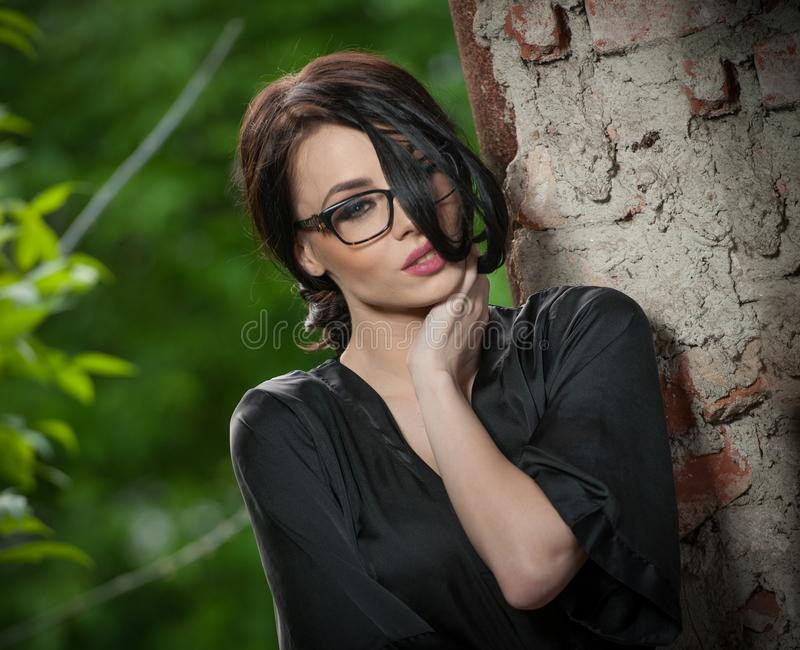 Mujer joven del retrato con la seda que viste el vestido negro y los vidrios que se inclinan contra la pared y la presentación At imagen de archivo libre de regalías