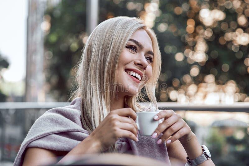 Mujer joven del retrato con los vidrios que bebe el café en café Relájese foto de archivo