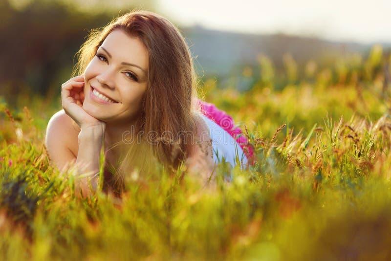 Mujer joven del retrato en el prado en un día de verano caliente fotografía de archivo