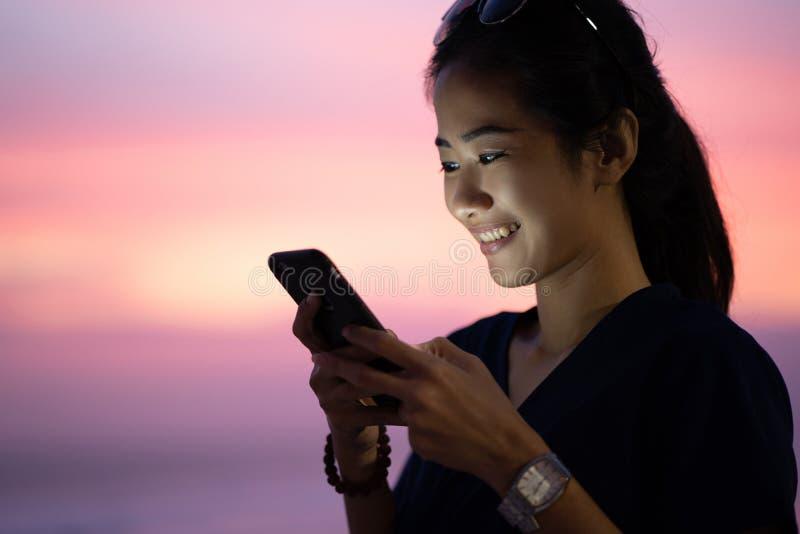 Mujer joven del retrato que usa smartphone imagenes de archivo